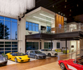 Commercial Office Studio featuring car collection with Corvette, Ferrari and Porche. Photo includes large windows with dusk light and second level conference room all with a modern style.