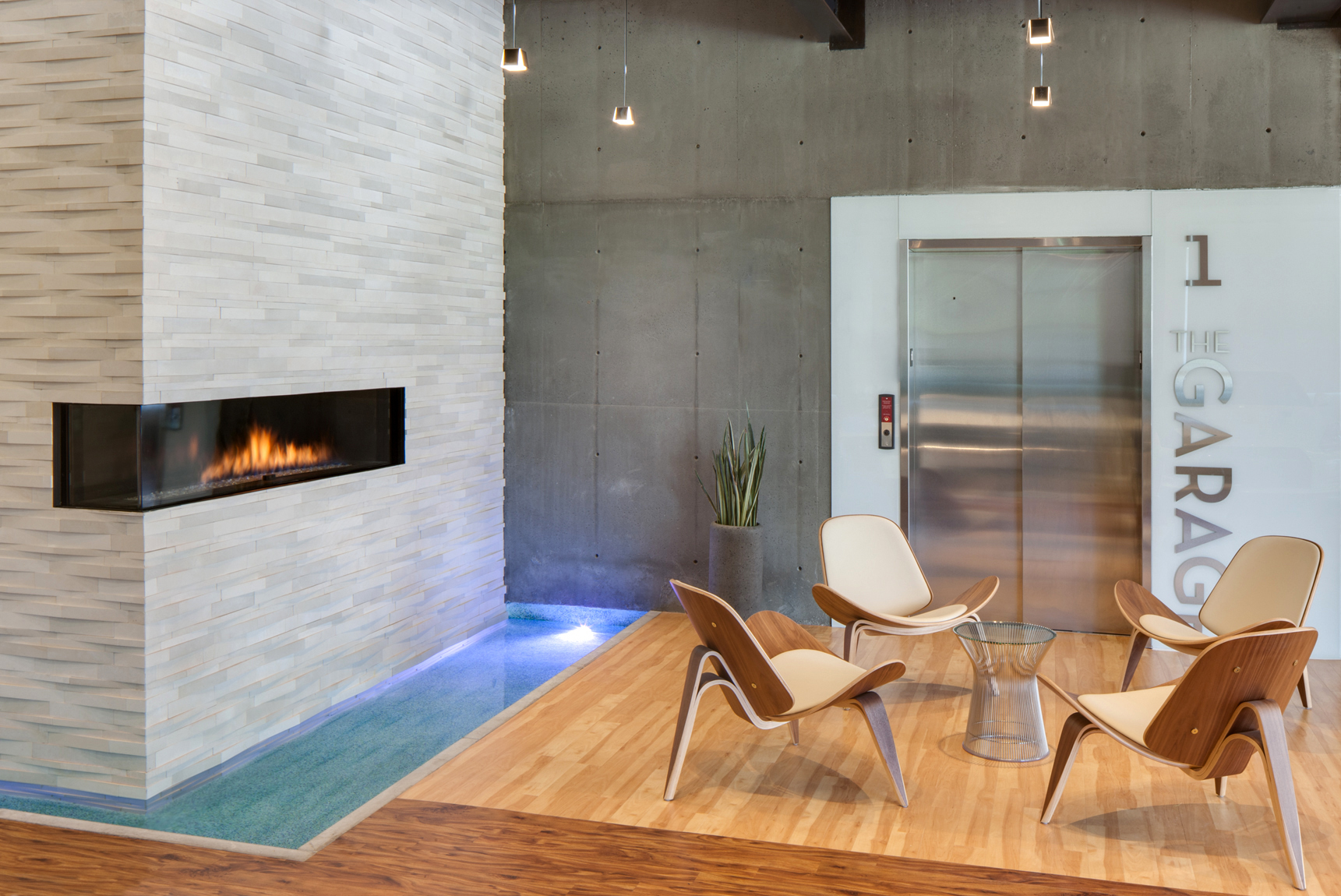 Modern office space with gas fire place, wood furniture, a water feature and a stainless steel elevator.