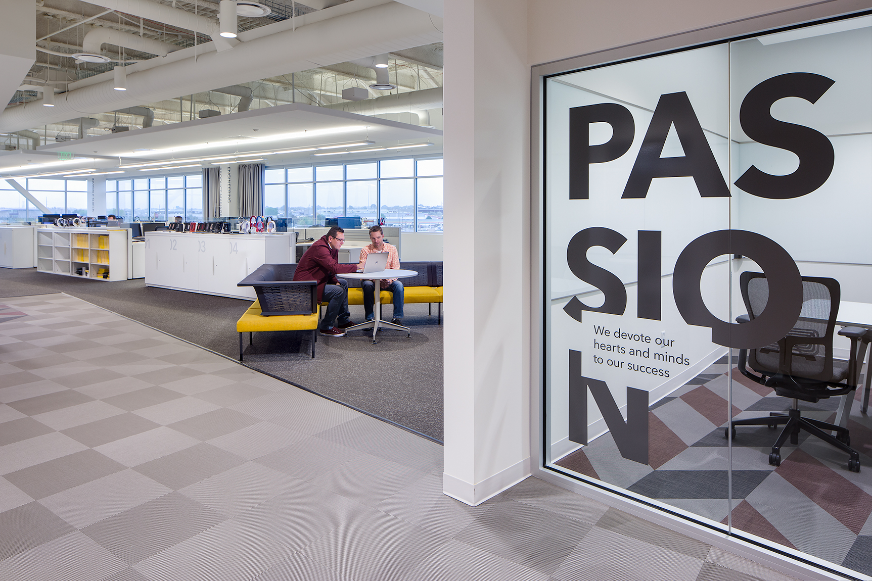 In the foreground of this photograph is a conference room with a glass enclosing wall with the words {quote}PASSION{quote} adhered to them. in the background, two employees are workingat a table in an open workspace filled with cubicles, other employees and product.