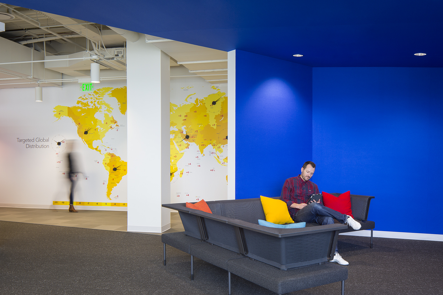 Man working on tablet in open walled room with blue felt walls while another employee walks in the backround against a global map wall.