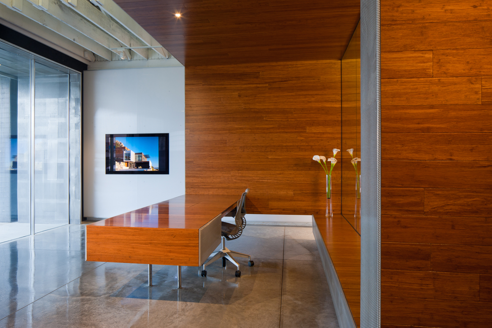 View of office conference room made of warm wood and glass with LED lights.