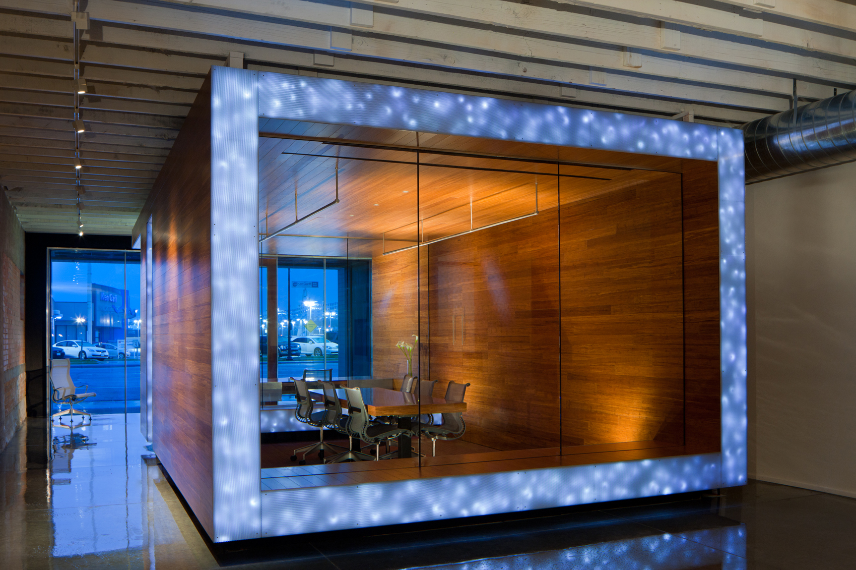 View of office conference room made of warm wood and glass with LED lights. Shiny concrete floors and blue, dusk windows.