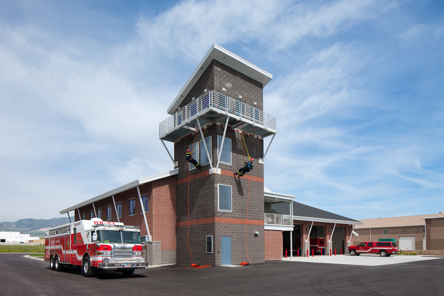 Exterior view of fire station with fire men rapelling from tower.