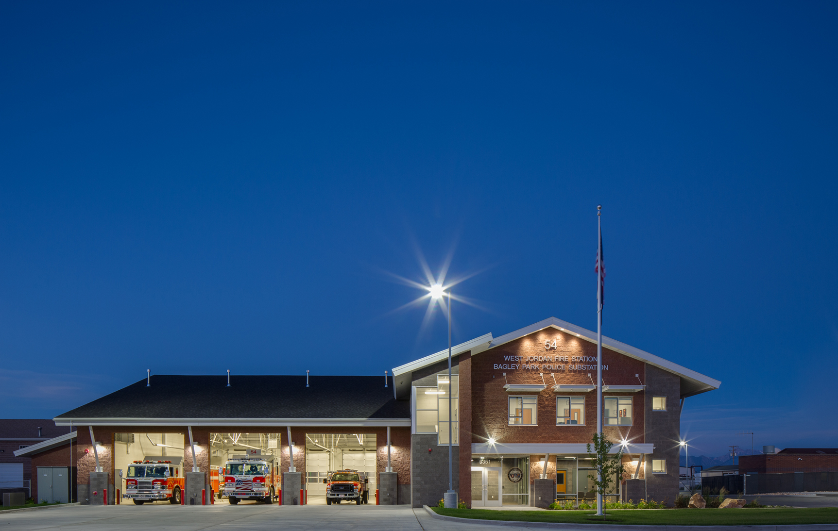 Exterior view of fire station at dusk with bay doors open and fire trucks in bays. Architectural Photography by: Paul Richer / RICHER IMAGES