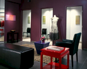 Interior view towards changing rooms in an upscale clothing boutique. Black leather furnishings are framed by maroon walls and the centerpiece features a bright red table.
