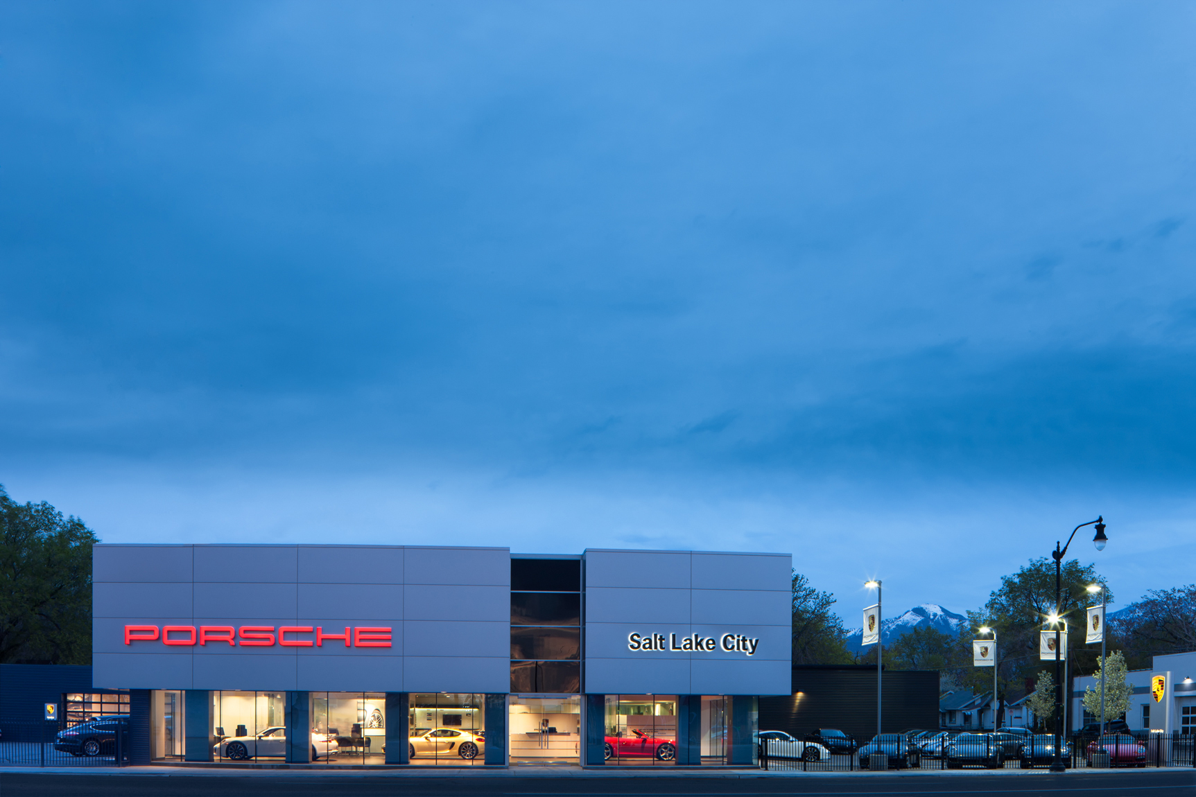 Exterior view of a Porsche Automotive dealership. The building is a modern, metal clad structure with large glass windows which highlight the showroom floor and the automobiles on it.