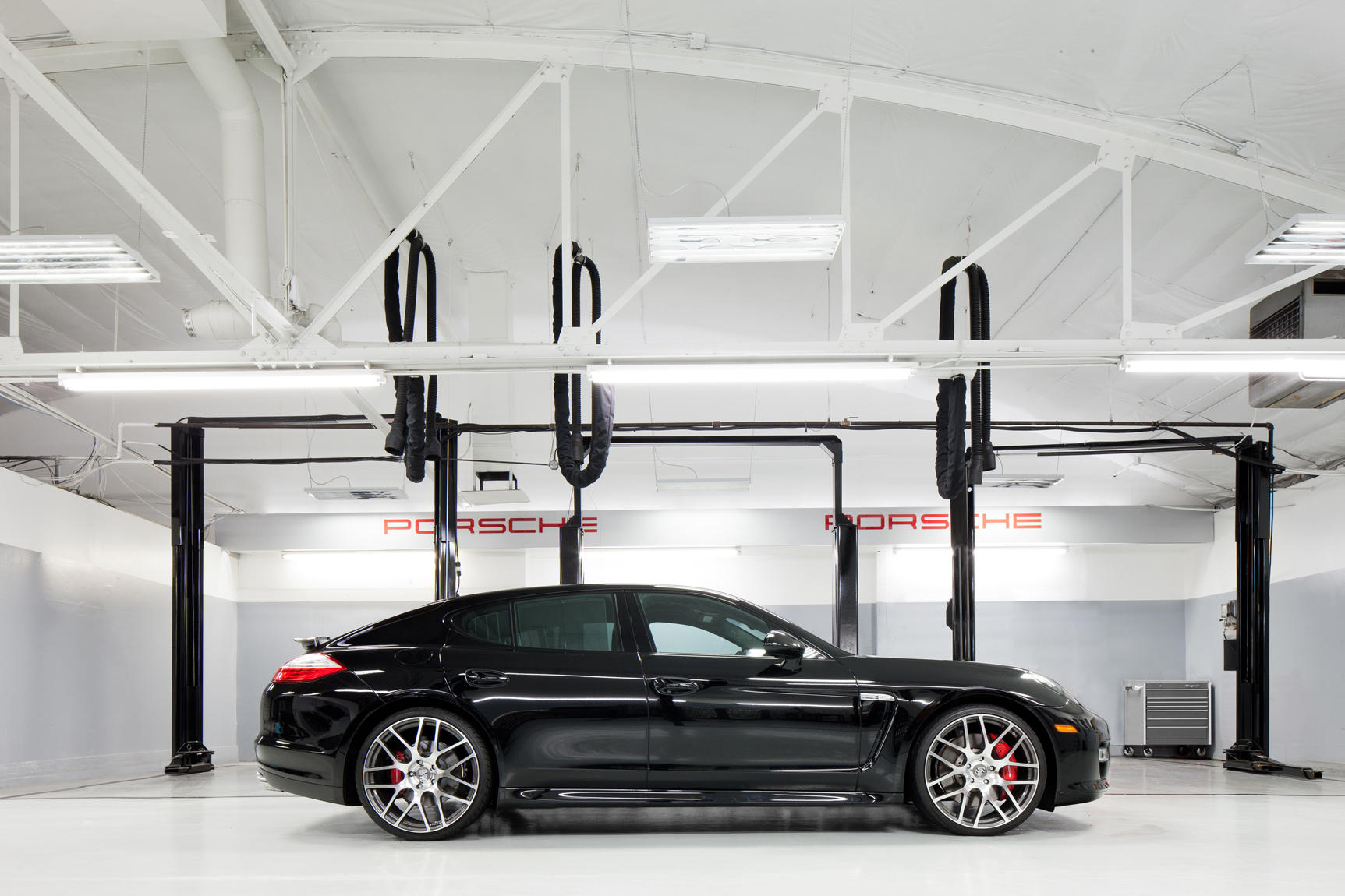 Interior high key, view of  black  Porsche Panamera in a service bay with white and gray walls.