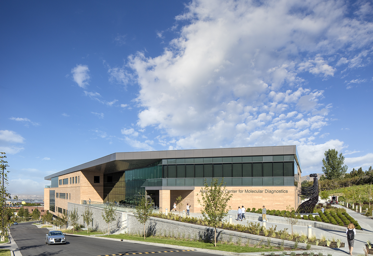Exterior photograph of a modern bio tech building under blue skies with big, puffy, clouds over head. The building has light brown masonry, large glass windows and people exiting the building.