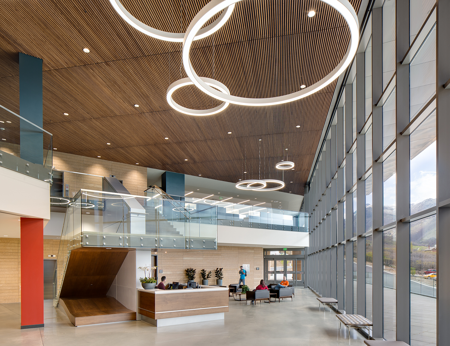 Interior view of a commmercial lobby space of a prominent bio tech company with tall glass windows, a two tiered floor plan, wooden ceilings and circular lights hanging from the ceiling.