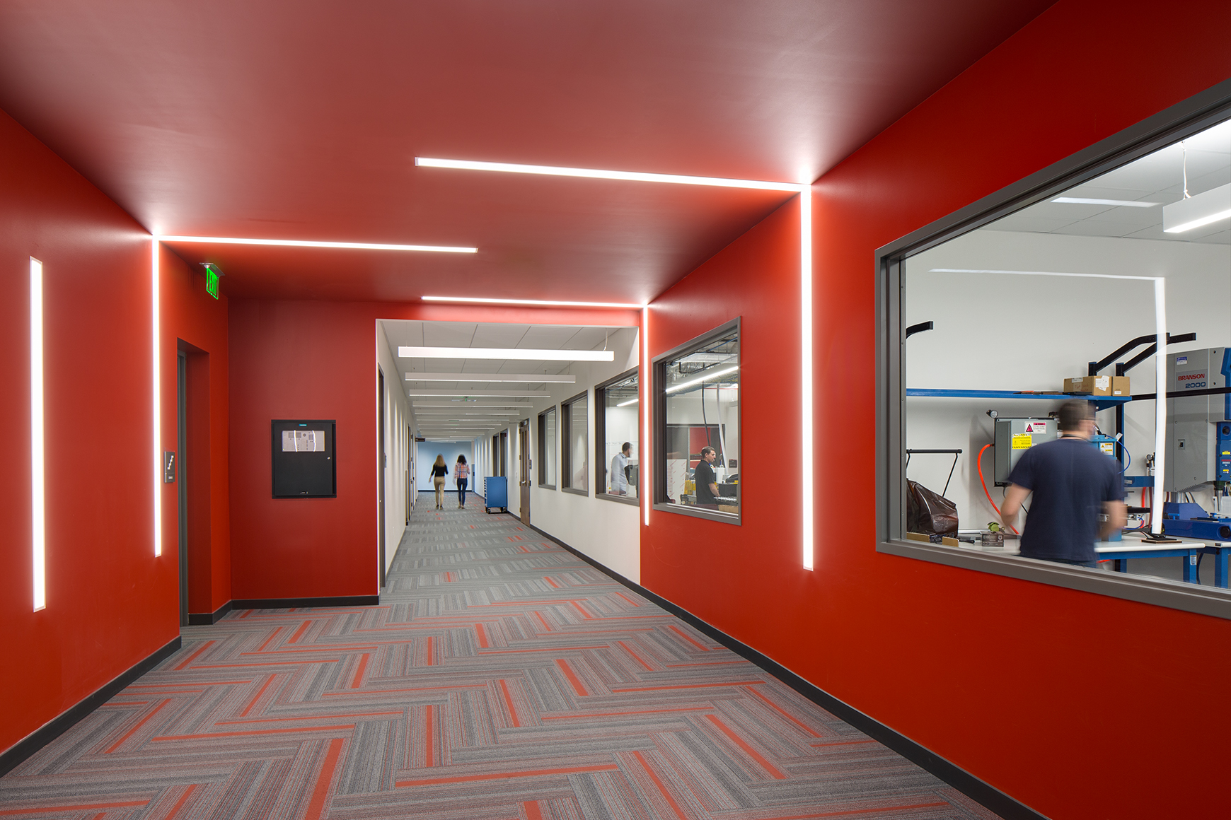 Interior photograph of long red hallway at Bio Fire, a bio tech company in Salt Lake City, Utah, with horizontal and vertical strip lighting on the ceilings and walls. The hall also has windows alloing for transparency into the lab spaces.