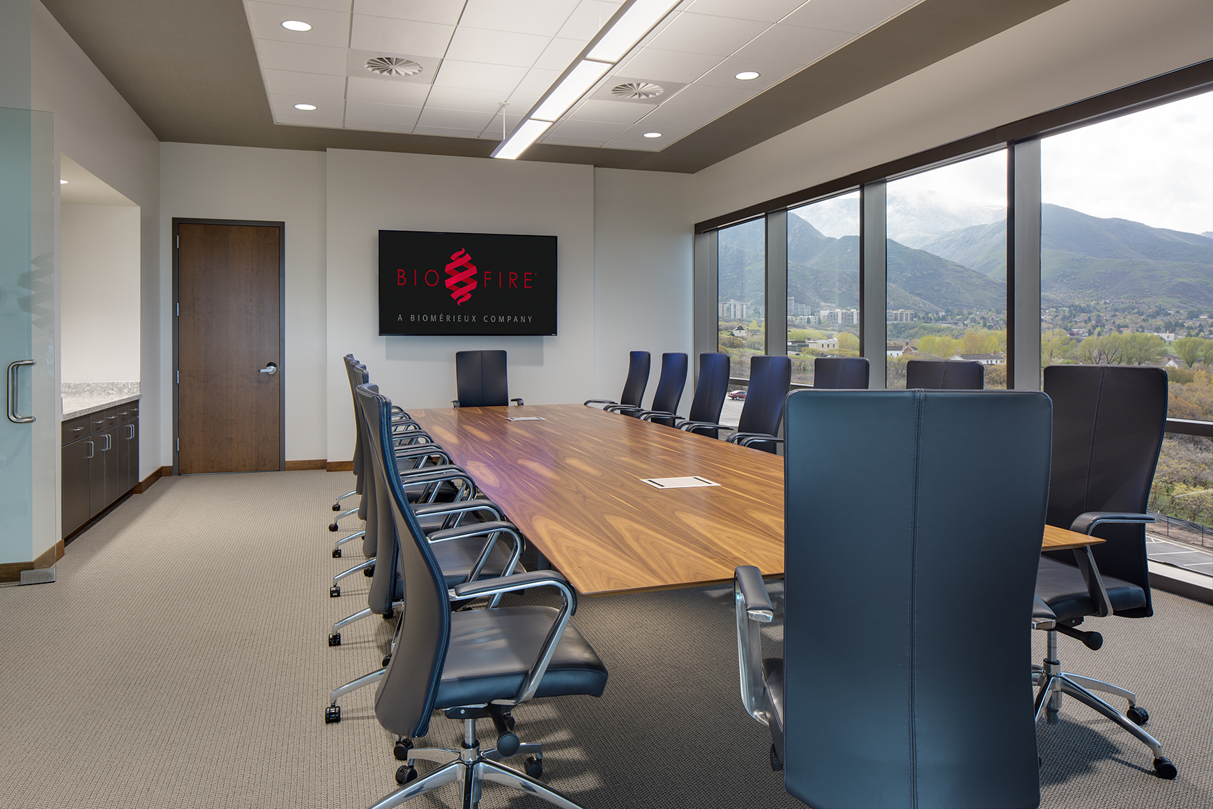 This photograph shows an interior view of a corporate boardroom with a long wood boardroom table, a monitor at the end of the table and floor to ceiling glass windows with views of mountains.