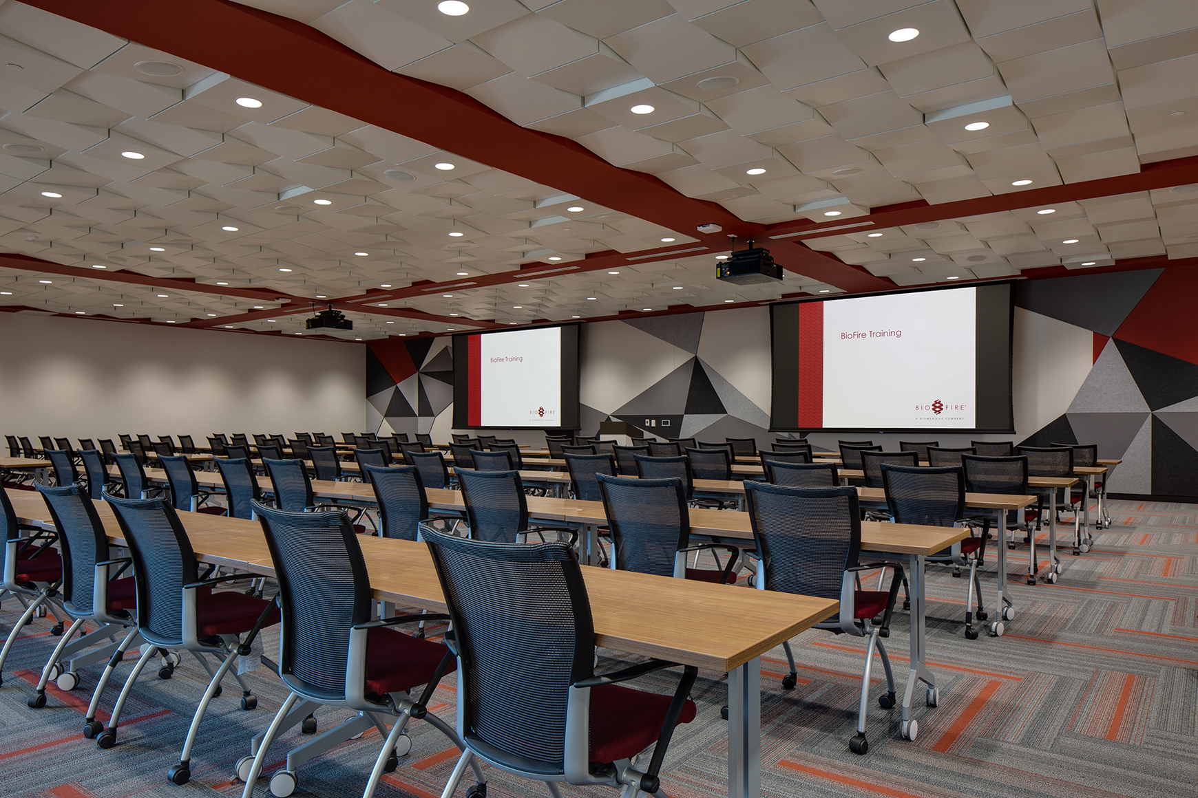This is an image, taken from the main entrance to the auditorium at a bio tech firm in Salt Lake City, UT. It features Herman Miller chairs in rows, accoustic panels on the ceilings and walls, two large display screens and moveable wooden tables.