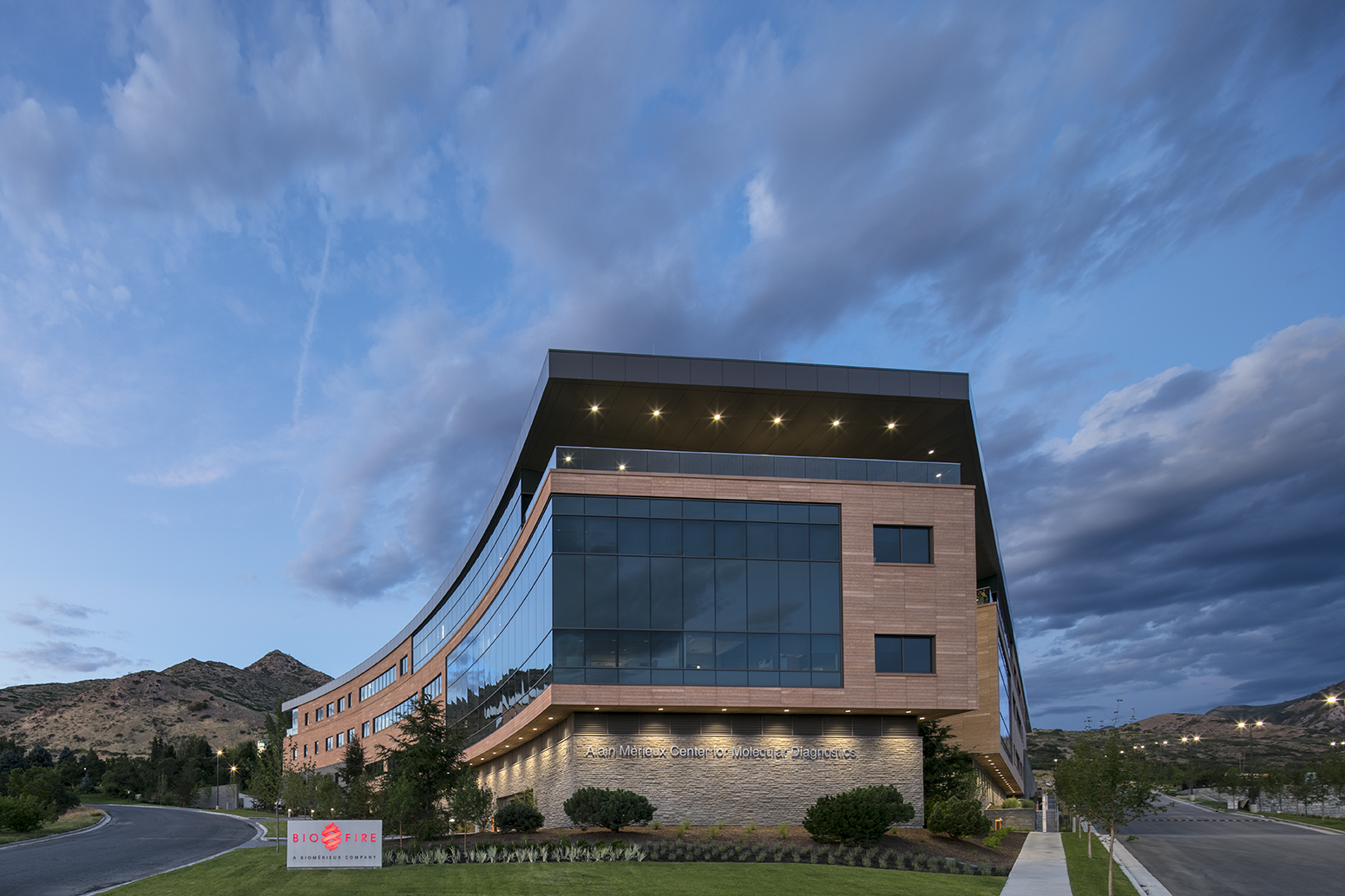 Exterior, architectural photograph of a modern biotech building under blue skies at dusk. The building is triangular in shape with a concave wall. The exterior is brick and glass and has an overhung roofline. on the bottom left is the Bio Fire signage.