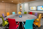 This photograph shows the viewer an interior of a corporate board room with a circular conference table and brightly colored chairs that surround it.. It has an overall modern feel and looks out the class door to the waiting area where a woman sits and speaks on her phone.
