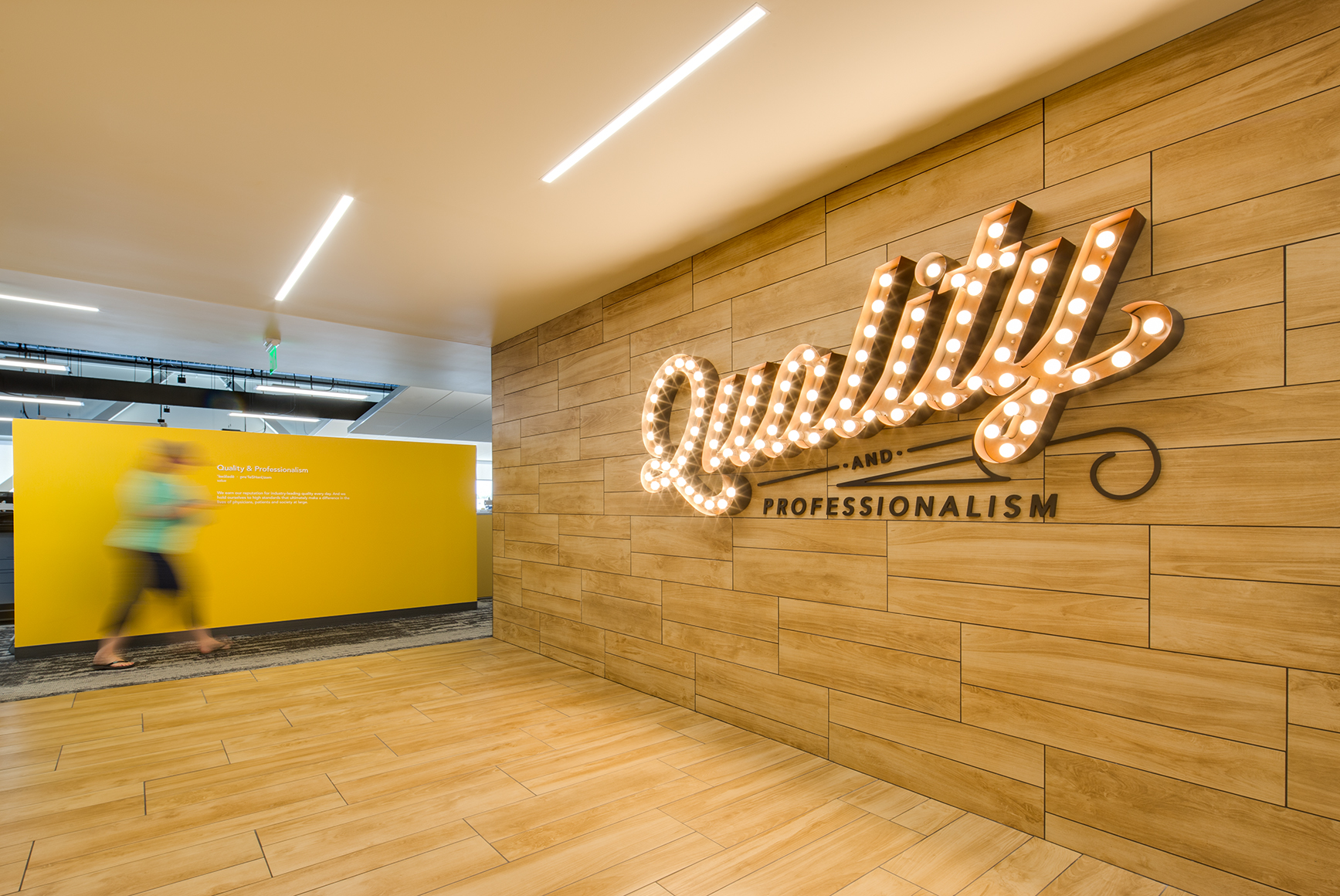 This interior architectural photograph shows a person walking in motion in corridor with yellow and wooden walls. On the wooden wall is a sign made of individual lightbulbs that reads {quote}Quality{quote}.