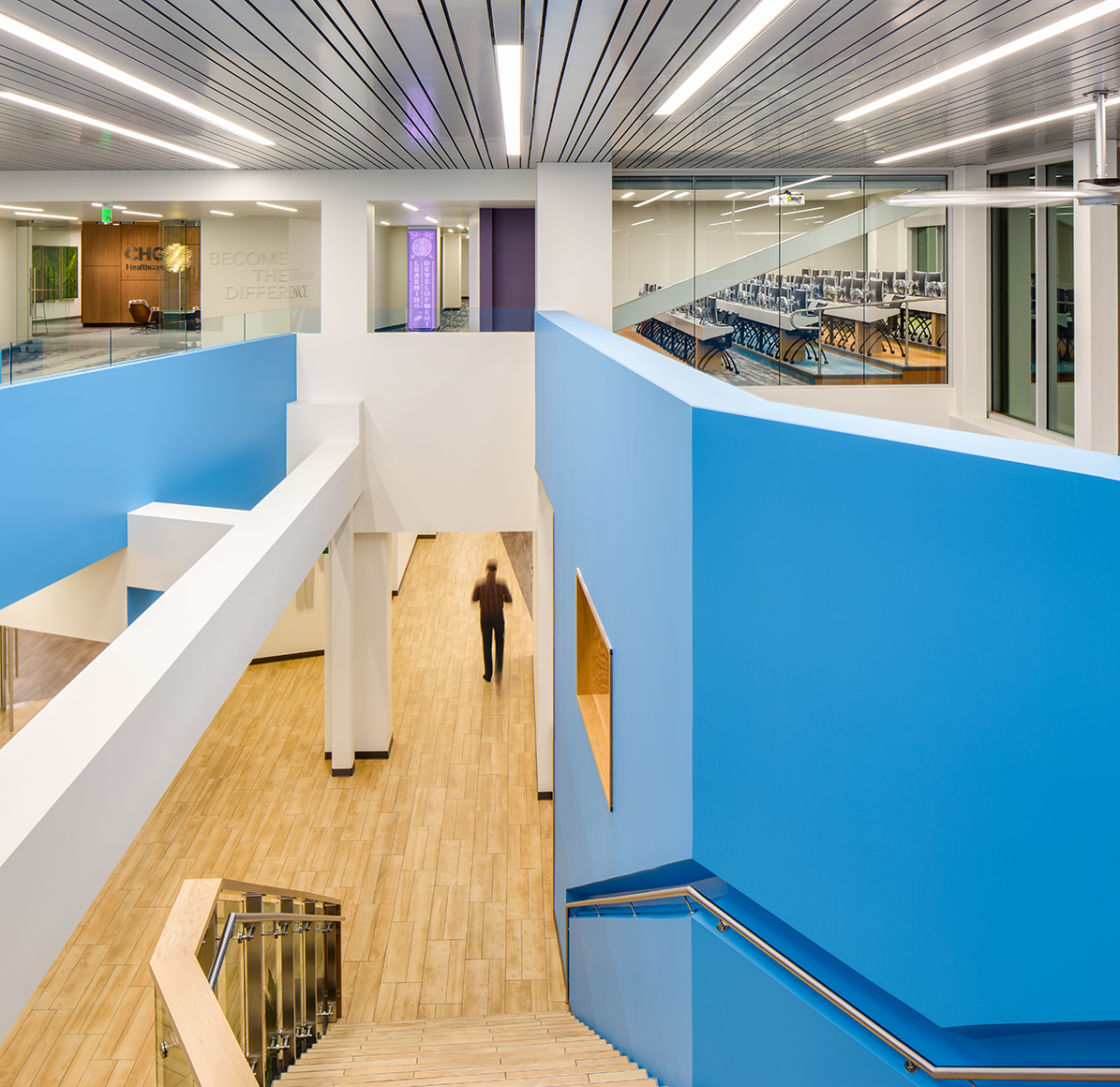 This architectural, interior photograph shows the viewer a camera angle taken from the second  level looking down a modern stairwell in an office space of a person on the first floor walking away. The walls are blue, the floors are wood and we see a glass enclosed traing room and an entrace to the corporate suites on the second floor.