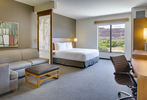 Daylit photograph of a comfortable suite at the Hyatt Hotel in Moab, UT. The viewer sees a modern desk and sofa in the forground with a kingsize bed next to the window that has views of thr red rock country and green cottonwood trees