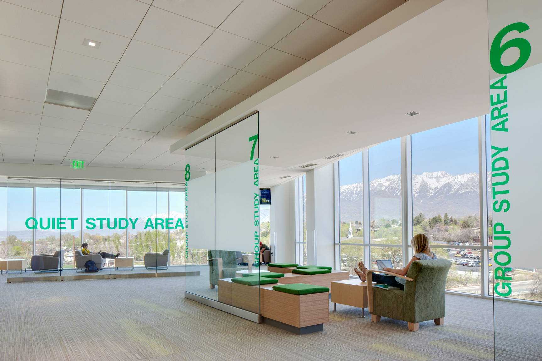 Students studying in quite area with tall glass windows and mountain views ant Utah State University.Architectural Photography by: Paul Richer / RICHER IMAGES