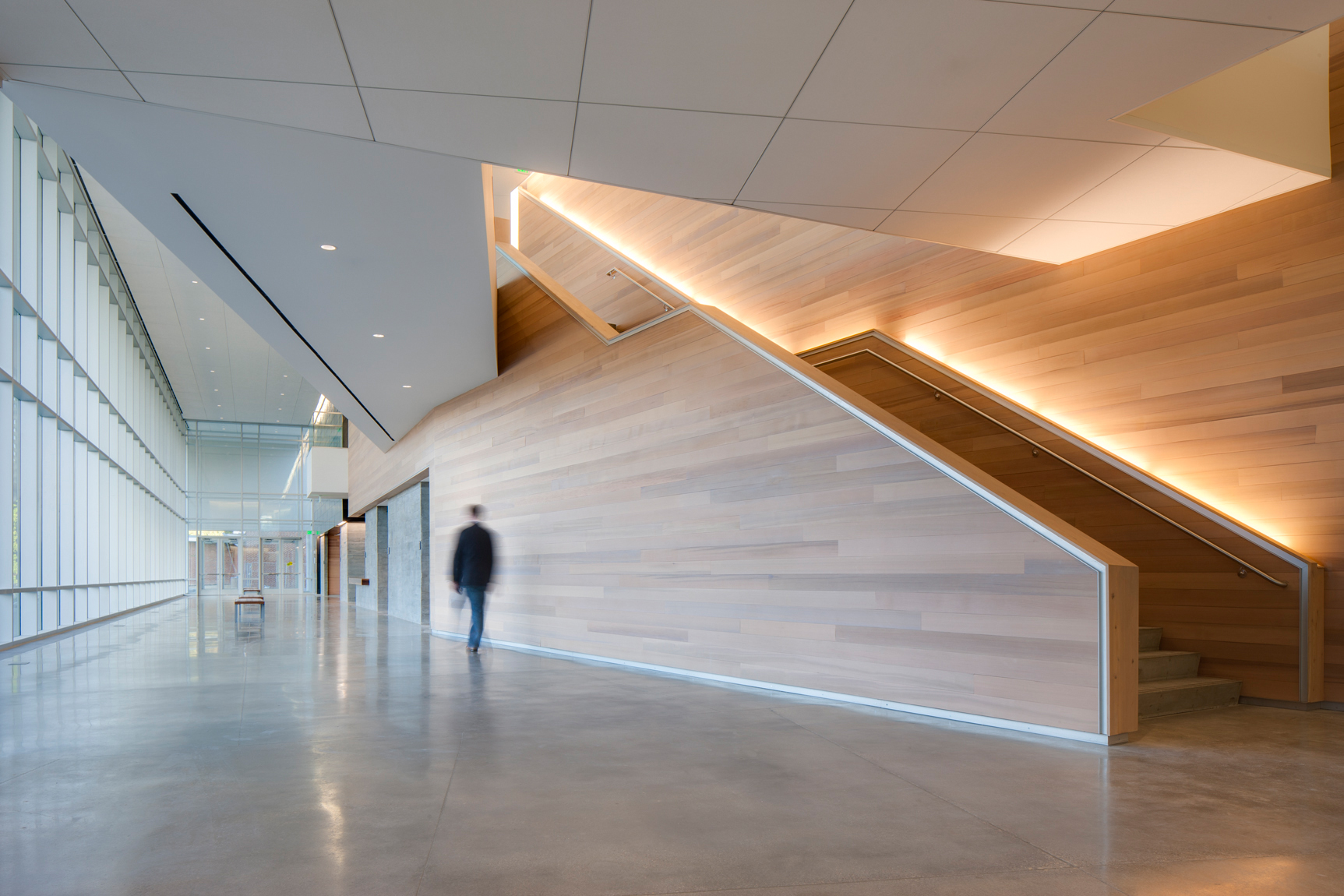 Motion blur of man walking down well lit corridor with large glass windows and sleek wooden stairwell