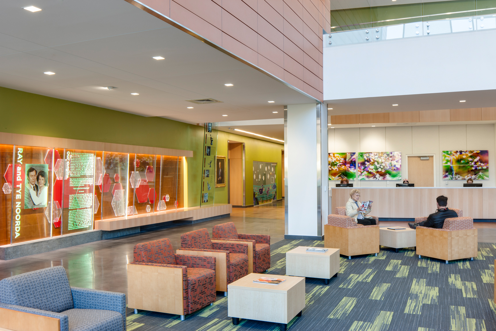 Interior lobby space of the U of U Oral Health & Sciences Building with illuminated displays explaining the history of the program, a reception desk and comfortable seating for the patrons.Architectural