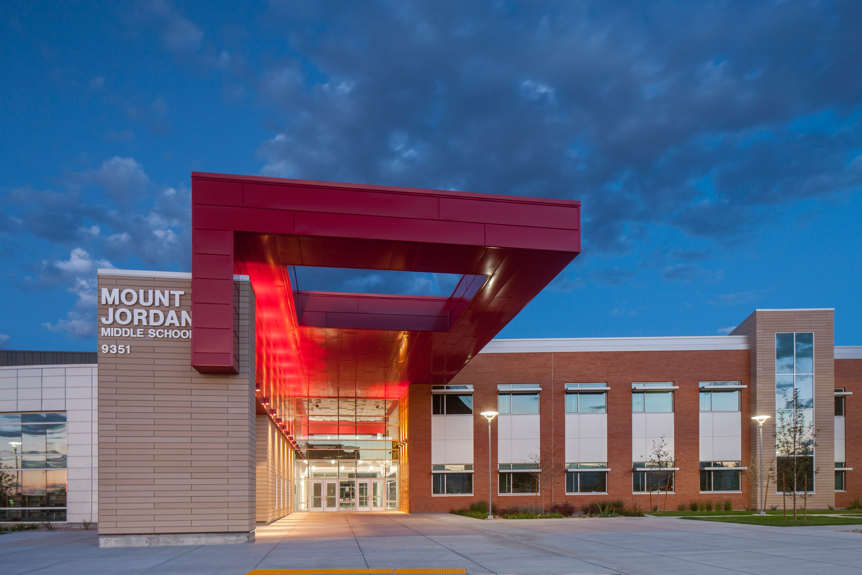 Architectural view of red canopy, entrance to middle school, at dusk. 