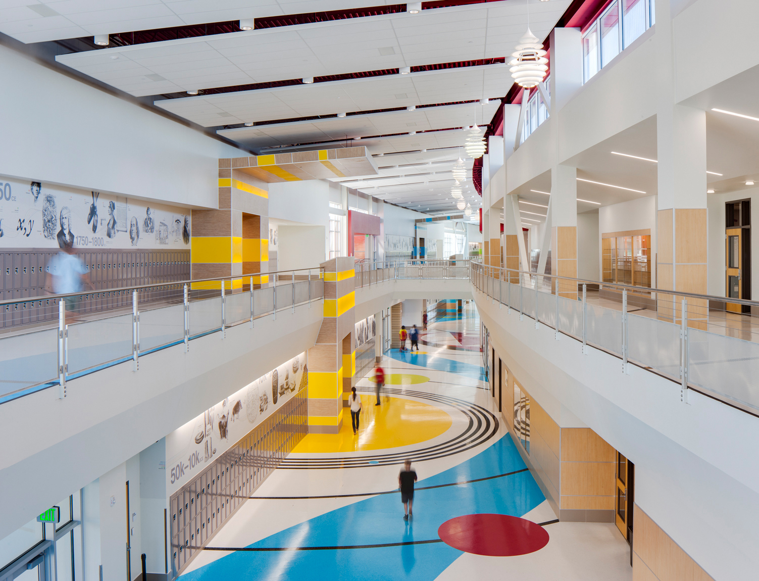 View down curved main hall of middle school with students in motion. MHTN Architects / Hogan & Associates