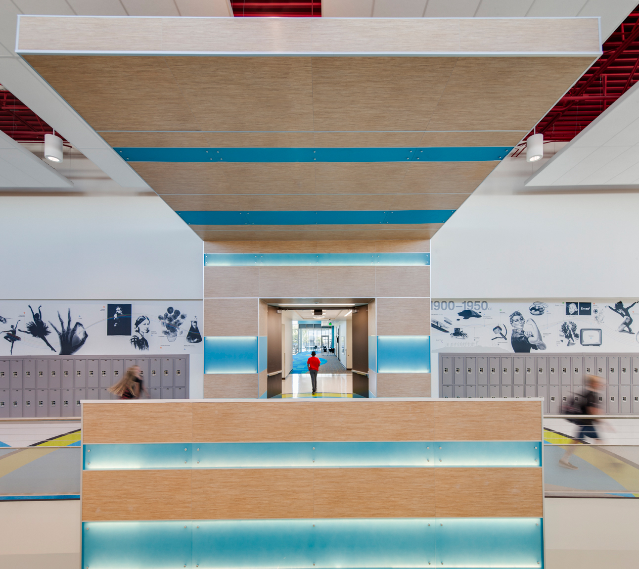 View looking down class room wing atMt. Jordan Middle School in Sandy Utah for MHTN Architects / Hogan & Associates. The canopies feature wood and stripes of illuminated, colored palstic. This one is blue and has a boy in a red shirt running away from the camera.