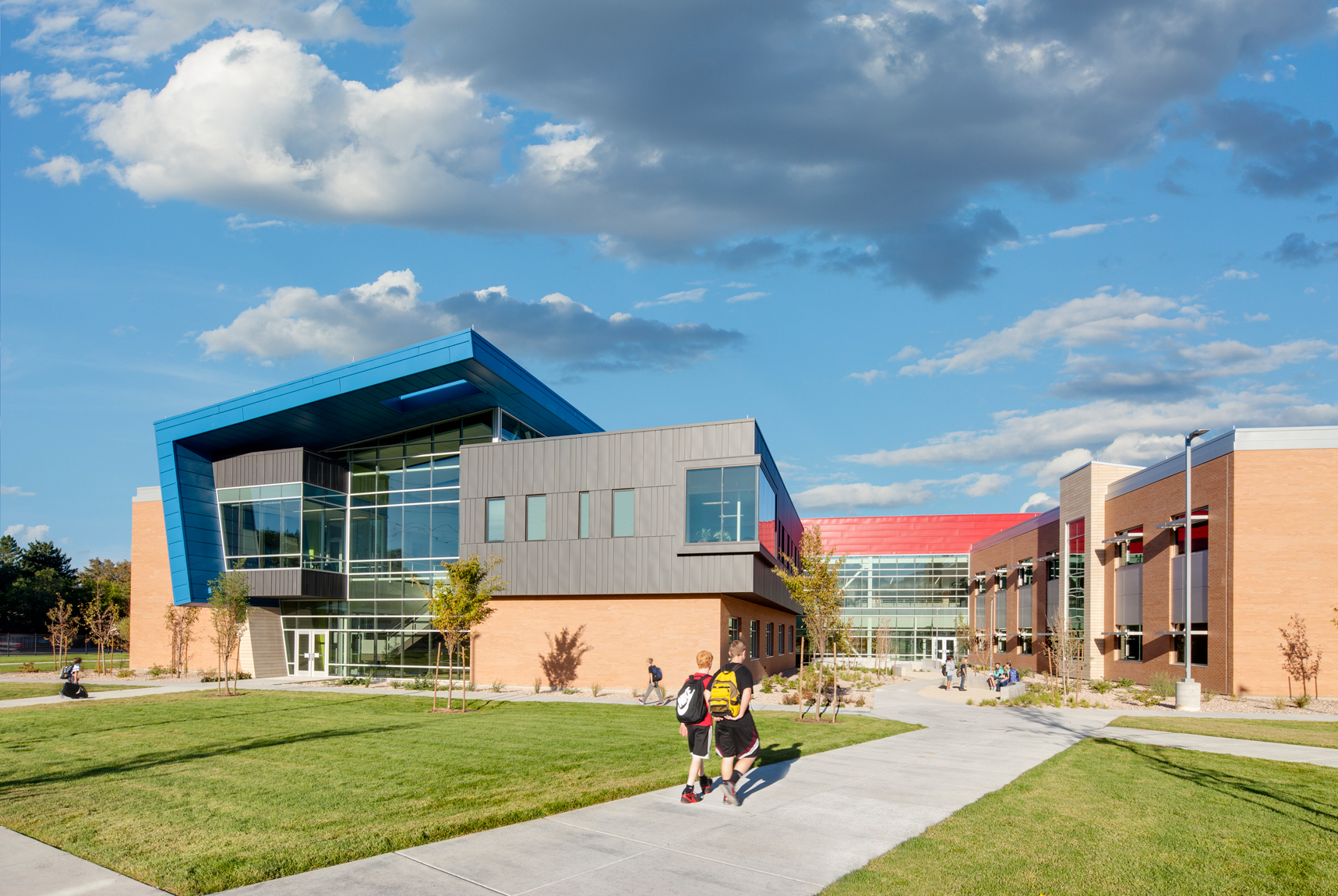Exterior view of classroom wing with students walking to calss at sunrise at Mt. Jordan Middle School in Sandy Utah for MHTN Architects / Hogan & Associates. These wings feature metal cladding and overhangs of blue metal. Architectural Photography by Paul Richer / RICHER IMAGES