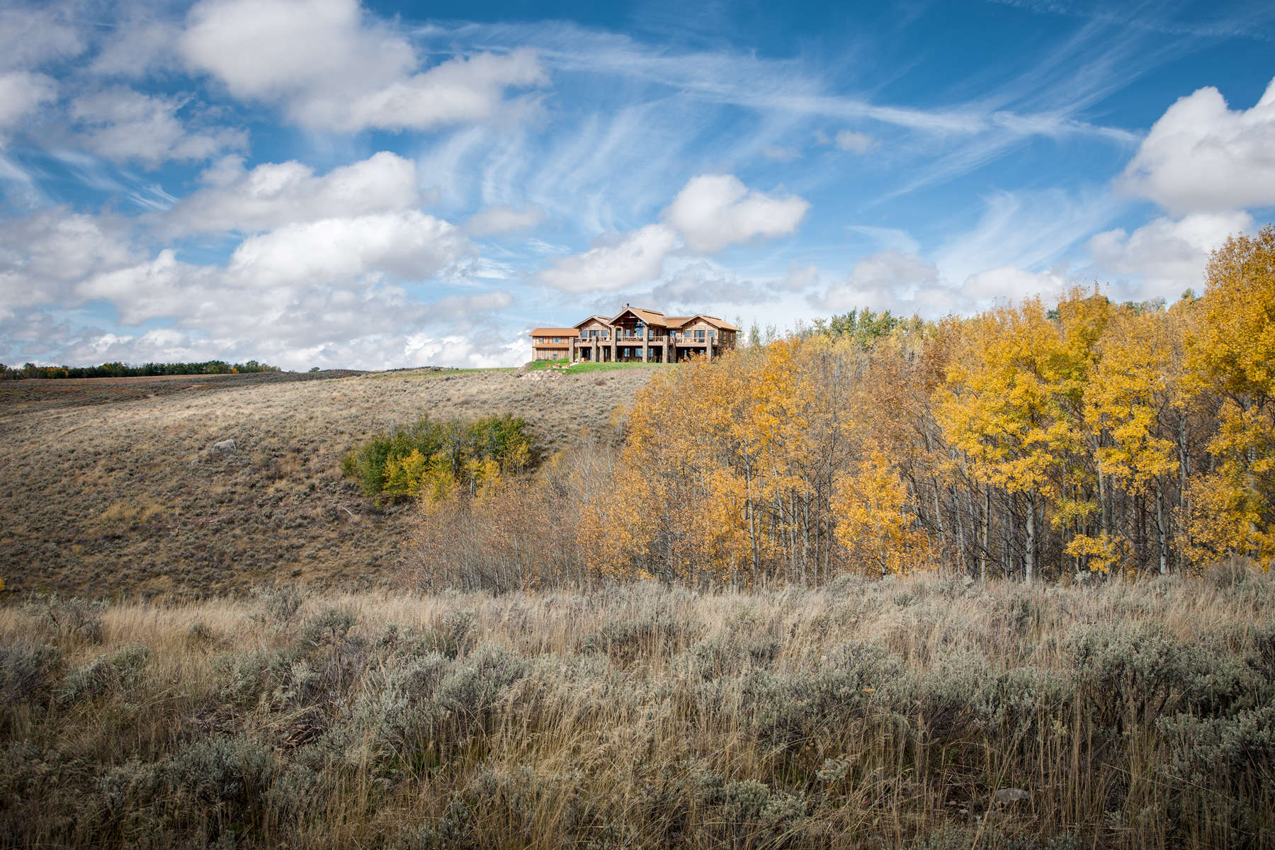 Long distance view of a mountain rustic home surrounded by rolling hills and golden stands of Aspen trees in eastern Idaho.