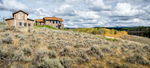 Long distance view of a mountain rustic home surrounded by rolling hills and golden stands of Aspen trees in eastern Idaho.The viewer can also see an old train trestle which has been converted to a bike path.