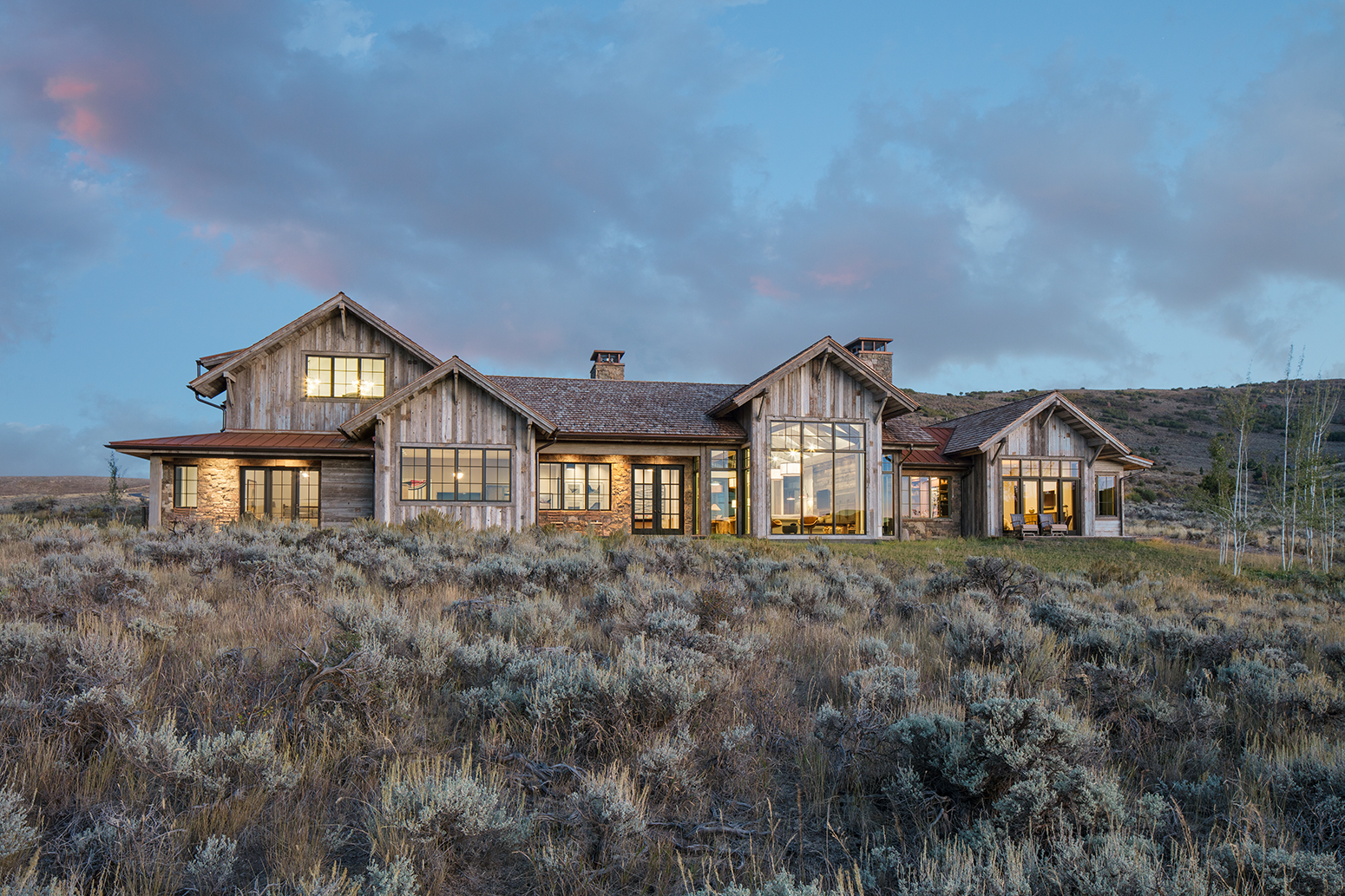 This is a picture of a rustic, luxury home in a meadow of sage brush. The photograph was taken at dusk so the clouds are pink, the skies are blue and a warm glow is radiating from the windows.