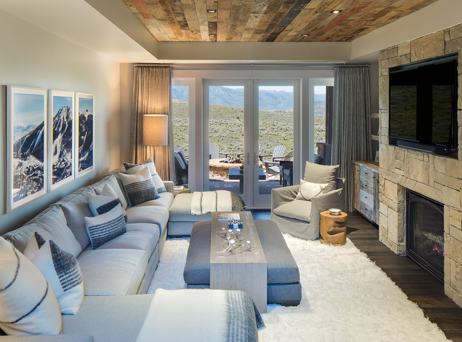 This is an interior photograph of a a tv room / den in a mountain rustic home. The viewer is looking through the room from a slightly elevated height and out the double glass doors on the far side with views of rolling sage hills and mountains in the backround. The floor has a faux sheep wool carpet with the ceiling covered in reclaimed wood planking. On one side of the room hangs a tv mounted in a stone floor to ceiling section with a gas firplace and on the other side of the room is a wrap around couch.
