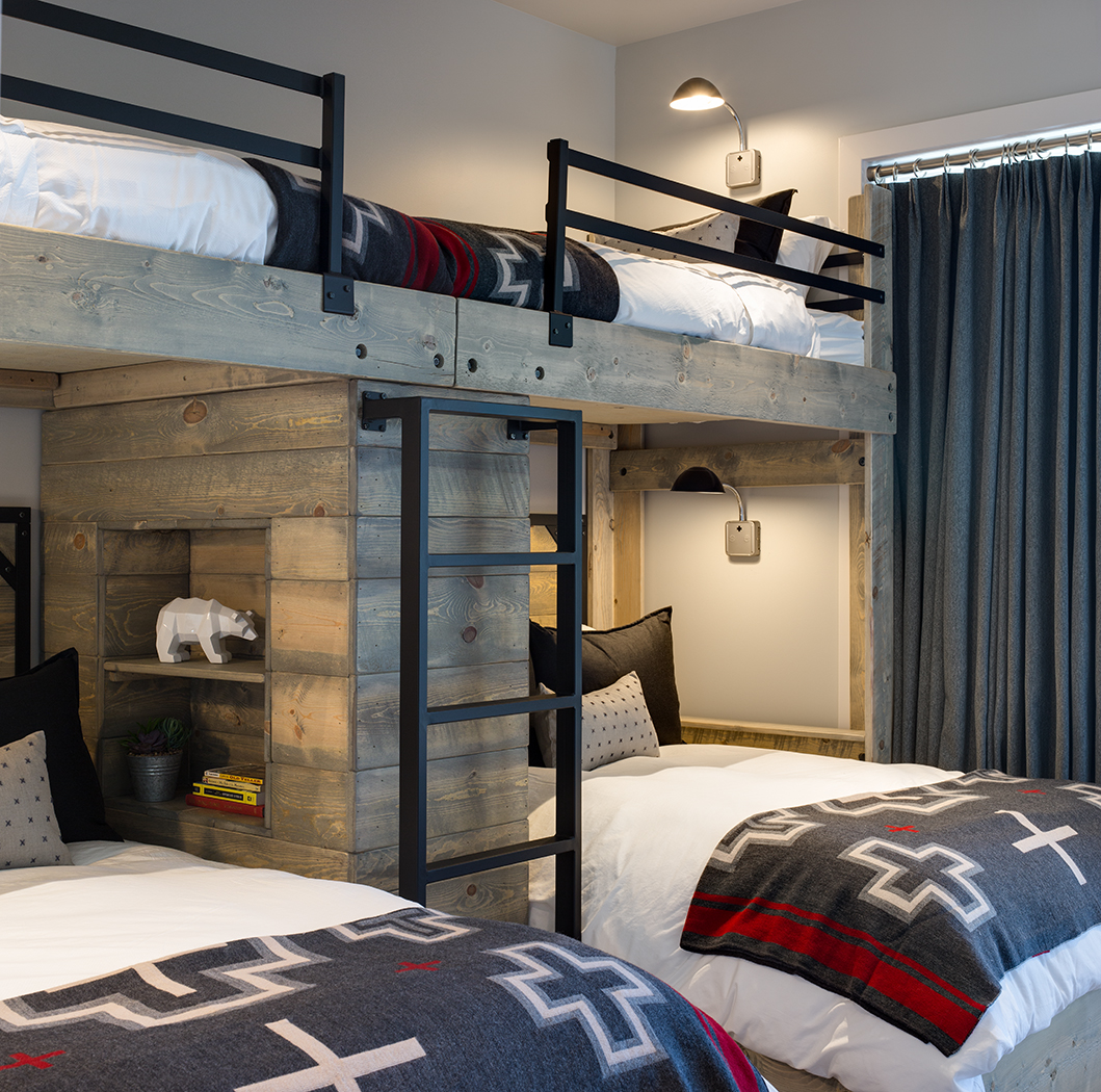This is an interior photograph of a bunkroom for kids in a mountain modern rustic residence. There are four beds in all and the lower beds have built in cubbies with individual wall lights. There are pillows and black steel rails and a ladder.