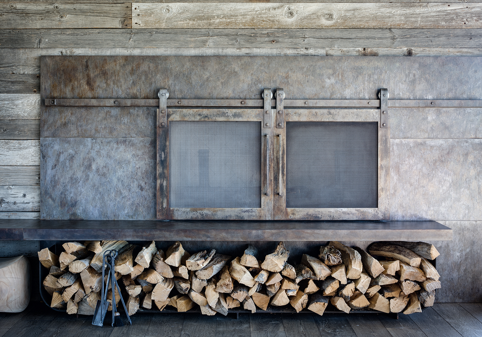 This is a photograph of a custom built firepalce in a mountain rustic home near Park City, UT. The fireplace is encased in distessed steel and surrounded by a wall clad in reclaimed timber.