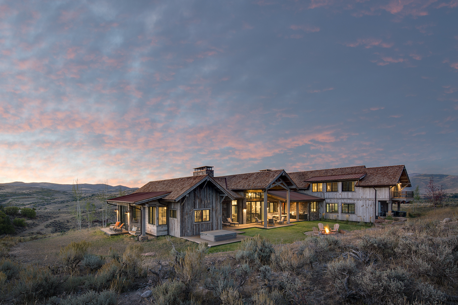 This is an exterior photograph of a new, rustic residence at sunset situated in the foorthills near Park City, Utah, surrounded by sage and rolling hills. The lights are on in the home and their is transparence in the windows allowing the viewer to see in to the house. There are colors of blue, magenta and pink in the skies and their is an outdoor fireplace which is lit and surrounded by two Adirondack chairs. The house is clad in reclaimed timber and blends in naturally with the surrounding landscape.