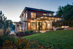 Exterior photograph of the back veranda and yard of a modern home in a residential neighborhood known as the Avenies at dusk in Salt Lake City, UT. Ther veranda has sparkling lights draped above the concrete sitting area with an open fire pit lit and flames.
