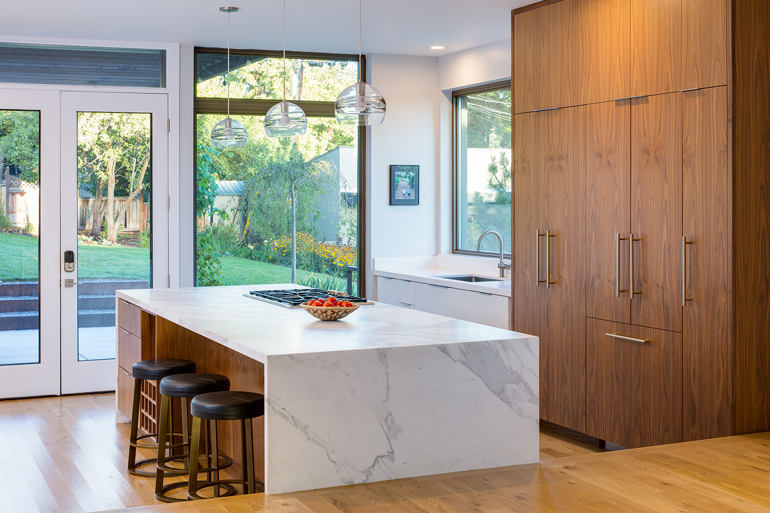 This is a photograph of a kitchen in a modern home with a large marble island with a bowl of red timatos on it.. Through the windows and doors the viewer sees the spacious, green back yard.