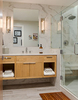 This is a photograph, looking through the door, of a residential bathroom. The viewer is looking directly at the sink, with wood cabinets below and towels in cubbies built in below the sink. To the lookers right there is a large shower with marble backsplash.