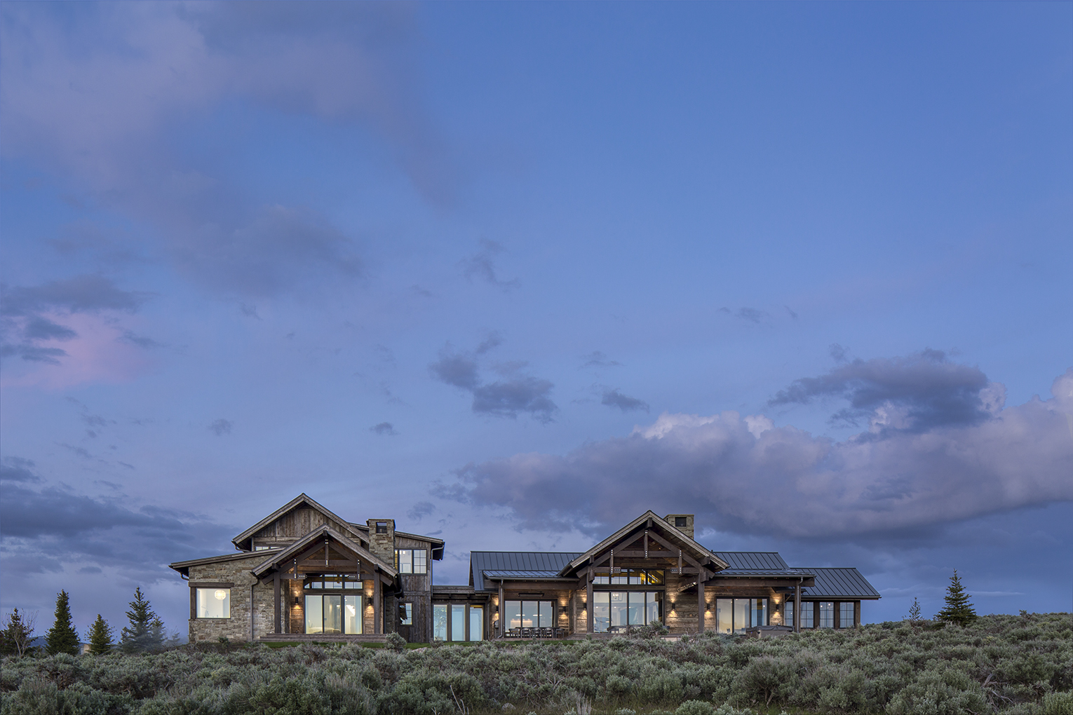 exterior photograph of luxury residence at dusk near Park City, Utah. The image shows dramatic skies and the home is clad in natural wood with warmth radiating from a lit interior.
