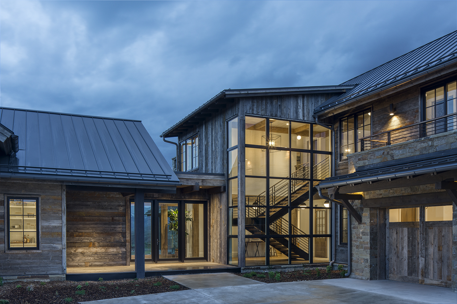 Exterior photograph of luxury residence at dusk near Park City, Utah. The photograph shows the main entrance with large glass windows that exposes the viewer to a beautiful stairwell  on the interior. The exterior of the home is of reclaimed lumber.