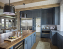 Interior photograph of a residential kitchen with views beyond to the dining area and beyond to the mountains of Park City, UT. All of the cabinets are blue and the ceiling is white bead board with exposed timber beams.