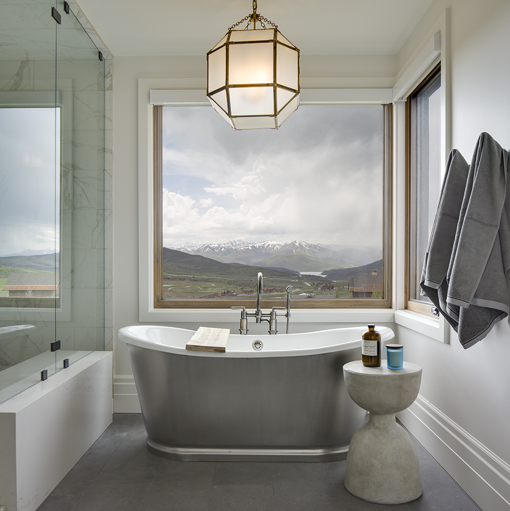 This is an interior photograph which features a bath tub in the master bathroom. The tub is placed up against the window with views of Deer Valley ski resort across the valley.