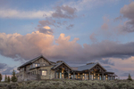 Exterior photograph of a private residence near Park City, UT. The house is surrounded by sage plants and dratic skies at dusk and the home is clad in reclaimed wood that looks very natural.