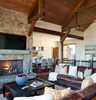 View of main living room in a mountain rustic home in eastern Idaho. The dining area can be seen in the back of the photo and in the forgrround we see a lit fireplace with a coffee table and a leather couch.Architectural Photography by: Paul Richer / RICHER IMAGES.