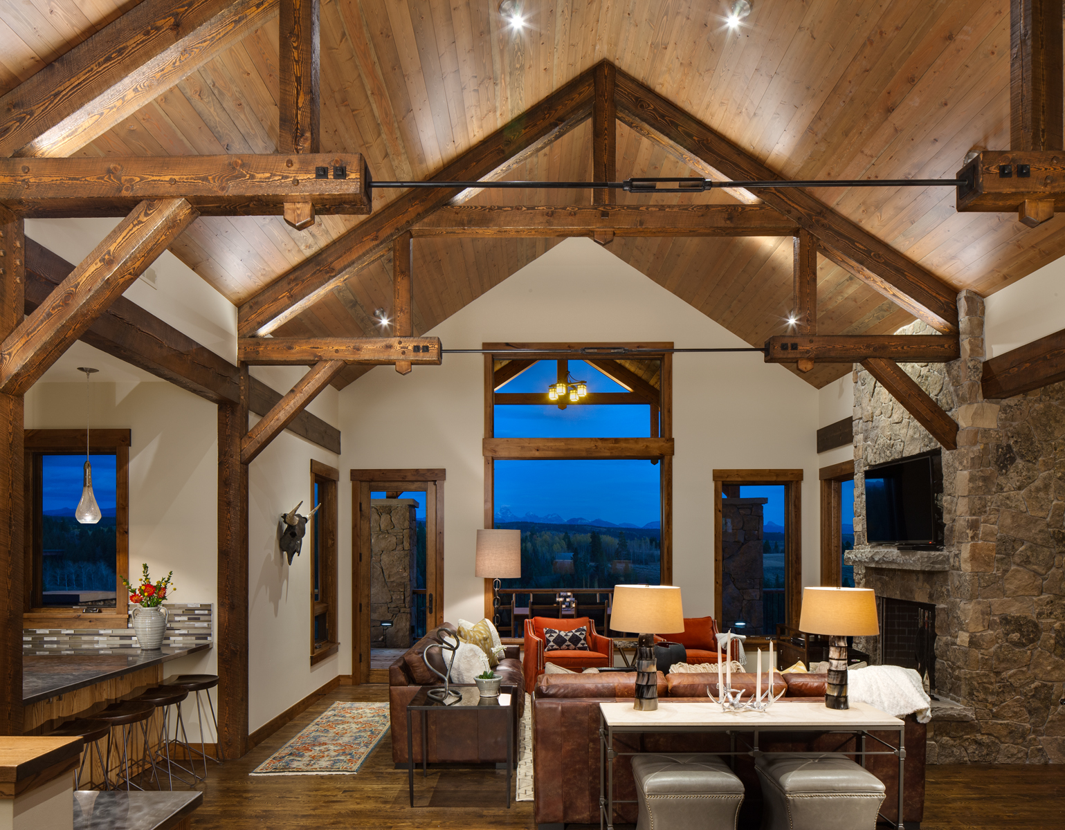 Interior view of living room at dusk with distant views of the Tetons. The room has a nice warm feel to it which reveals the natural tones of the wood floors and beams through out. The kitchen bar top can be seen on the left while the stone fire place is on the right. The home has high vaulted ceilings.
