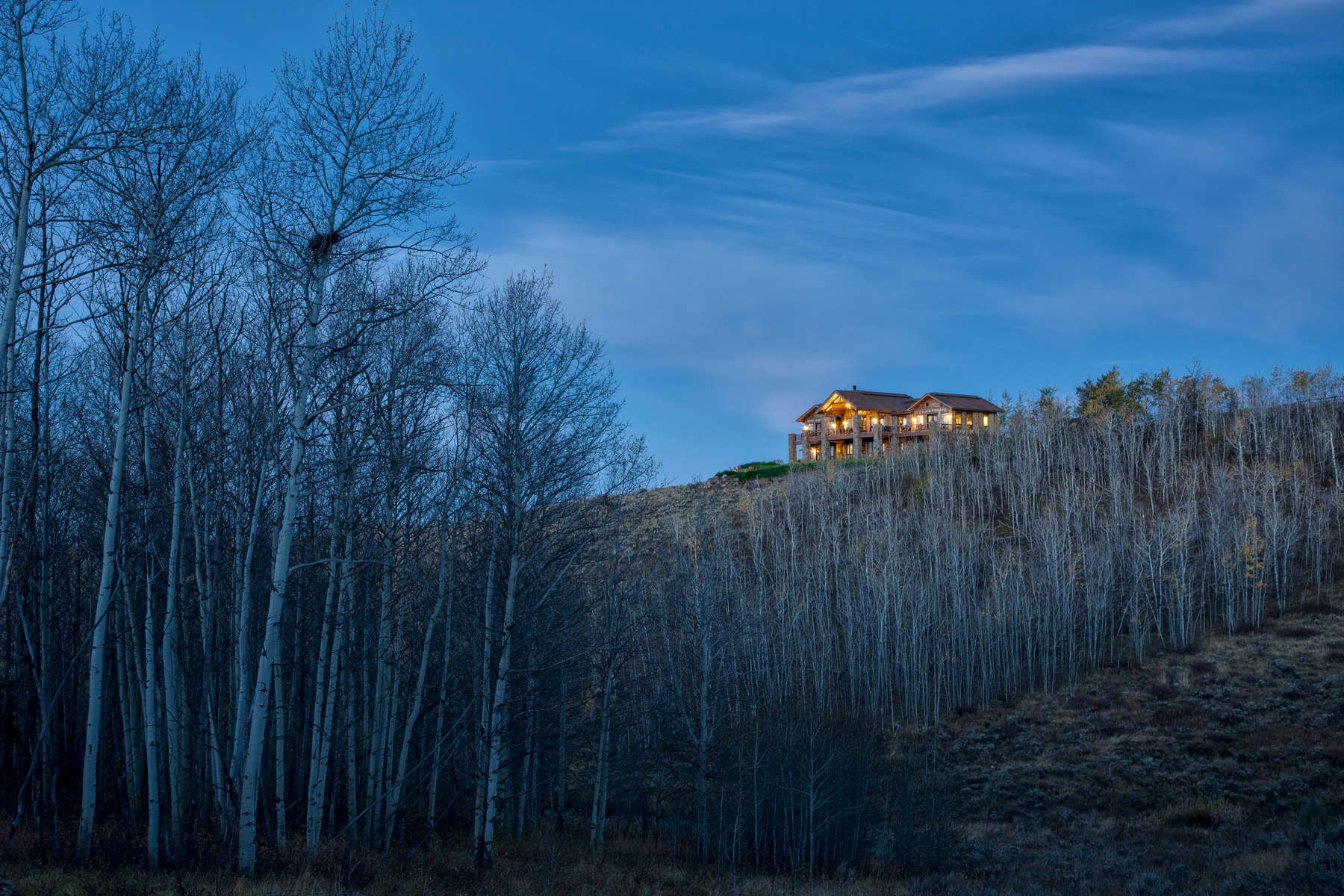 This is a long distance photograph of a private residence of a rustic home positioned on a ridgeline at dawn. The home radiates a warm orange glow and is framed by trees that have lost their leaves due to the time of year