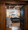 This is a photograph of a view into the master bedroom in a new but very rustic mountain home near Park City, UT. There is oak wood pannelling on the outside of the dor leading in and beautiful timbers that cris croos the ceiling above the master bed.