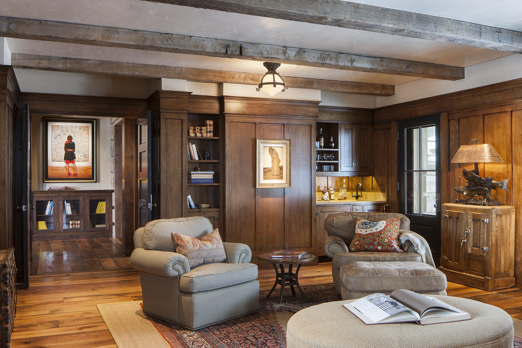 This is a view of a warm and cozy lounge room with wood walls and reclaimed timber ceilings. There is artwork on the walls and comfortable seating with a table and books. Architectural Photography by: Paul Richer / RICHER IMAGES.