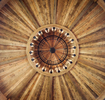 This is an interior detail of the rotunda of raw and reclaimed timber and the chandeleir in a private residence is the Shooting Star Development in Jackson, WY.