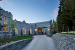 Exterior view at dusk looking up stone walled drive way of a Scottish manor house in Park City, UT with glowing windows.
